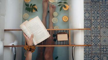 iemand leest boek in bad
