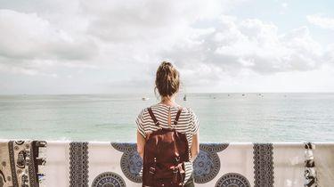 meisje kijkt uit op zee