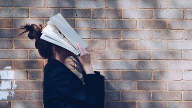 meisje is nieuwe taal leren met boek voor haar hoofd