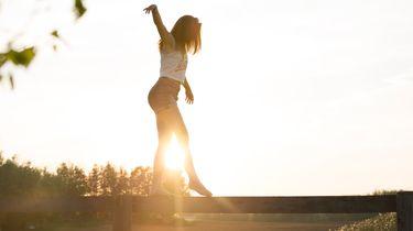 meisje balanceert op balk bij zonsondergang