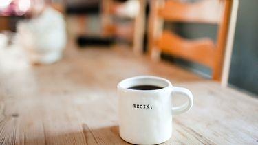 Koffiebeker waarop staat 'begin'