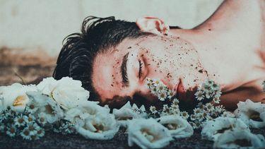 man ligt op grond met bloemen