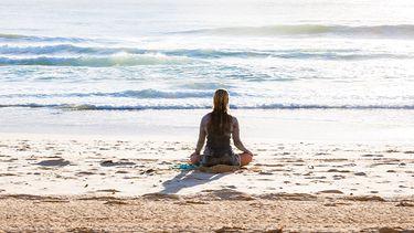 meisje doet kundalini yoga op strand