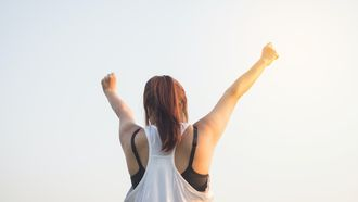 Vrouw in sportkleding die armen in de lucht steekt