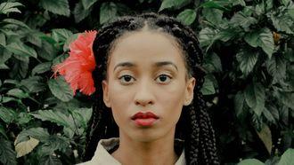 Vrouw kijkt recht in camera met bloem in haar