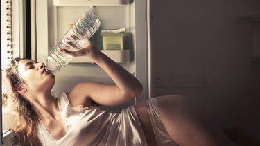 vrouw die water in de ochtends drinkt