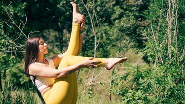 vrouw doet yoga in natuur