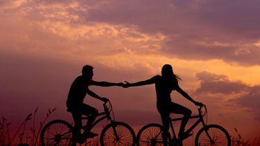 koppel op fiets die elkaar bijna loslaten