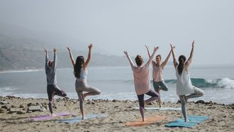 vrouwen doen yoga op het strand