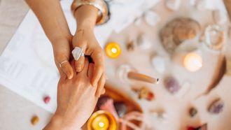Handen boven kaarsen en edelstenen