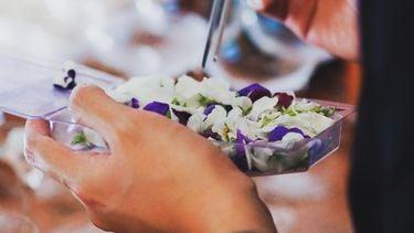 Persoon die eetbare viooltjes eet