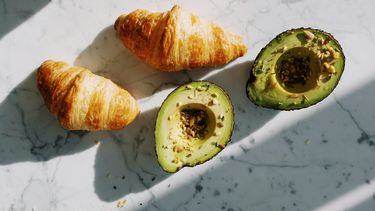 twee halve avocado's en 2 croissanten