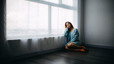 meisje zit met menstruatiepijn op de grond