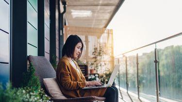 vrouw die aan het thuiswerken is op haar balkon