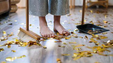 Voeten van meisje met bezem en confetti