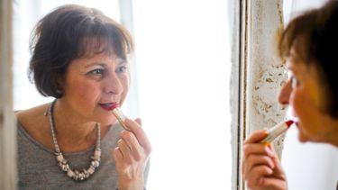 moeder doet lippenstift op