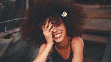 vrouw kijkt blij met bloem in haar