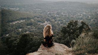 vrouw zit alleen op rots