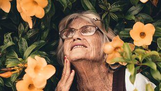 een oma met grijze haren voor een bosje met bloemen