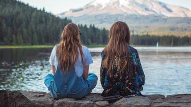 twee meisjes op een muurtje bij een meer