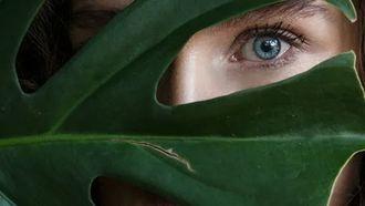 meisje verschuilt zich achter een blad