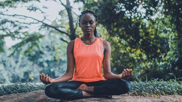 Vrouw mediteert in kleermakerszit