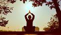 persoon mediteert met handen boven hoofd