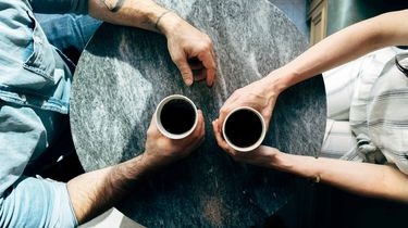 two person holding coffee