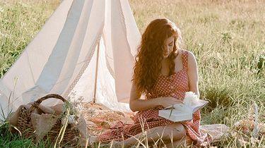 meisje leest boek in weiland