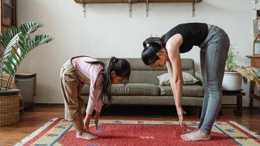 Moeder en dochter doen forward fold