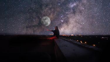Meisje zit op dak met volle maan en sterren op de achtergrond