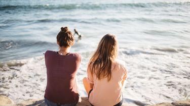 Twee vriendinnen zitten op het strand