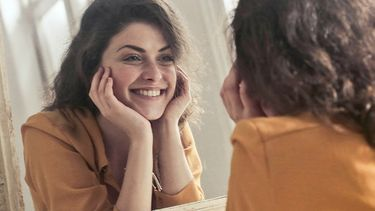 vrouw kijkt in spiegel