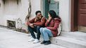 Twee mensen praten op de stoep