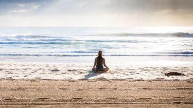 meisje mediteert op strand