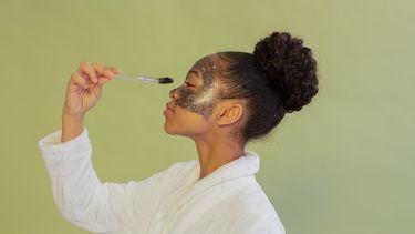 vrouw maakt zichzelf op met make-up en glitters