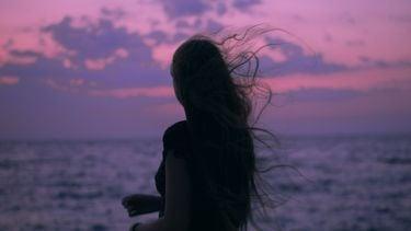 vrouw die naar de zee kijkt