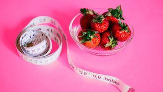 foto met een meetlint en aardbeien want het afvallen lukt niet