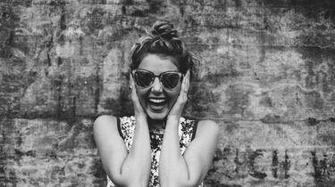 meisje lacht voor een muur