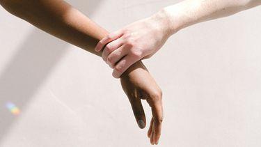 Een hand pakt een arm vast