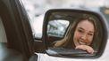 meisje lacht gelukkig in spiegel van auto