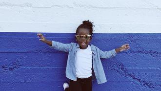 meisje met bril op voor paarse muur