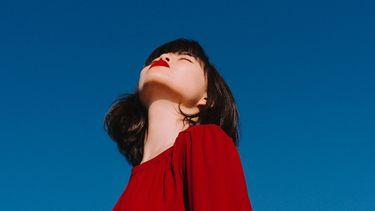 Vrouw met rode trui staat buiten