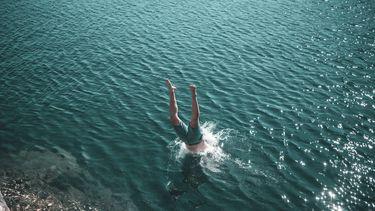 man duikt in meer