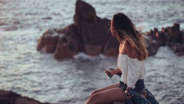 meisje zit op een rots voor zee
