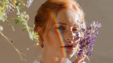 vrouw met regenboog op gezicht