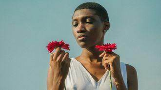 vrouw heeft bloemen vast en kijkt sip