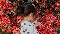 klein meisje voor een bloemenstruik