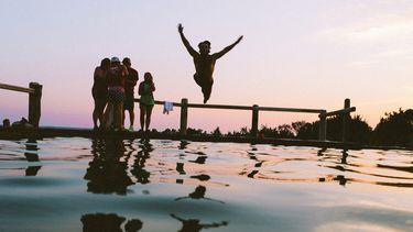 jongen springt in water