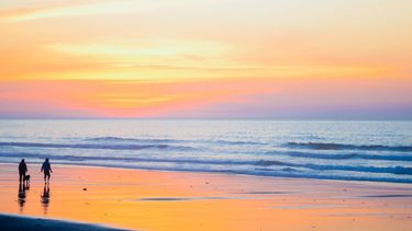 twee mensen maken strandwandeling
